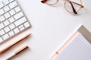 Klawiatura okulary i notatnik z długopisami