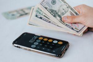Kalkulator i pieniądze trzymane w ręce