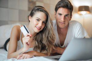 Kobieta i mężczyzna leżący przy laptopie z kartą kredytową